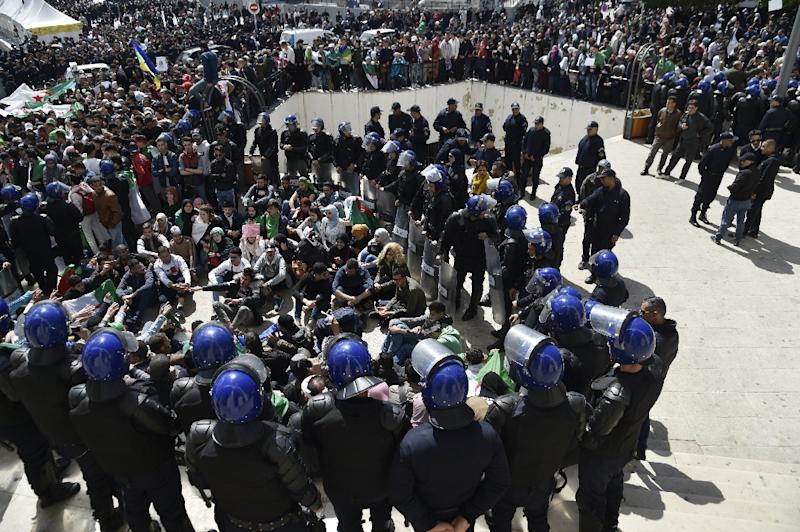 Algerian riot police come face to face with anti-government protesters in the capital Algiers (AFP Photo/RYAD KRAMDI                        )