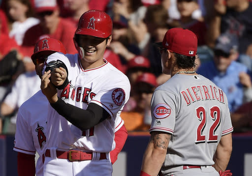 Los Angeles Angels' Shohei Ohtani, left, of Japan, talks with Cincinnati Reds first baseman Derek Dietrich after hitting a single during the first inning of a baseball game Wednesday, June 26, 2019, in Anaheim, Calif. (AP Photo/Mark J. Terrill)