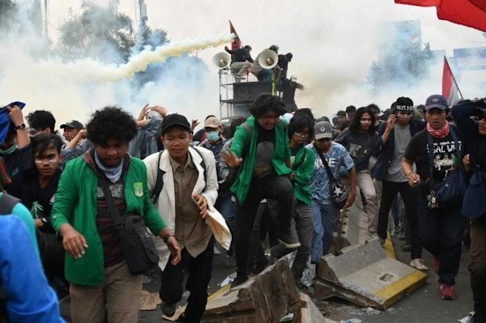 Student protesters flee as police fire tear gas during a demonstration in Jakarta (AFP Photo/ADEK BERRY)