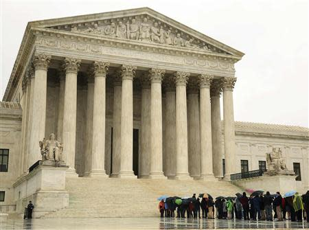 People line up in the rain outside of the U.S. Supreme Court in Washington in this April 29, 2014 file photo. REUTERS/Gary Cameron/Files