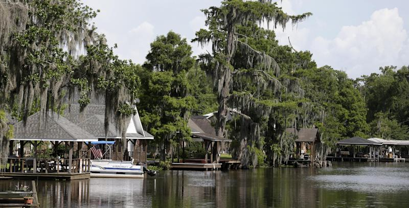 In this Thursday, June 27, 2013 photo, houses under a mandatory evacuation order, due to an approximate 22-acre sinkhole are seen along Bayou Corne, La. Neighbors in tiny Bayou Corne face a wrenching decision after a huge sinkhole opened up near their community: Do they stay put or should they pack up and move. The sinkhole resulted from a collapsed underground salt dome cavern about 40 miles south of Baton Rouge. After oil and natural gas came oozing up and acres of swampland liquefied into muck, the community's 350 residents were advised to evacuate. Texas Brine Co., the operator of the salt dome, is negotiating buyouts of residents who have not joined lawsuits against the company. (AP Photo/Gerald Herbert)