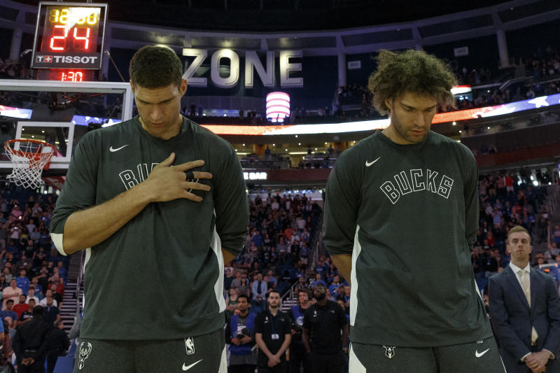 ORLANDO, FL - NOVEMBER 1: Brothers Brook Lopez #11 and Robin Lopez #42 of the Milwaukee Bucks during the National Anthem before the game against the Orlando Magic at the Amway Center on November 1, 2019 in Orlando, Florida. The Bucks defeated the Magic 123 to 91. NOTE TO USER: User expressly acknowledges and agrees that, by downloading and or using this photograph, User is consenting to the terms and conditions of the Getty Images License Agreement. (Photo by Don Juan Moore/Getty Images)