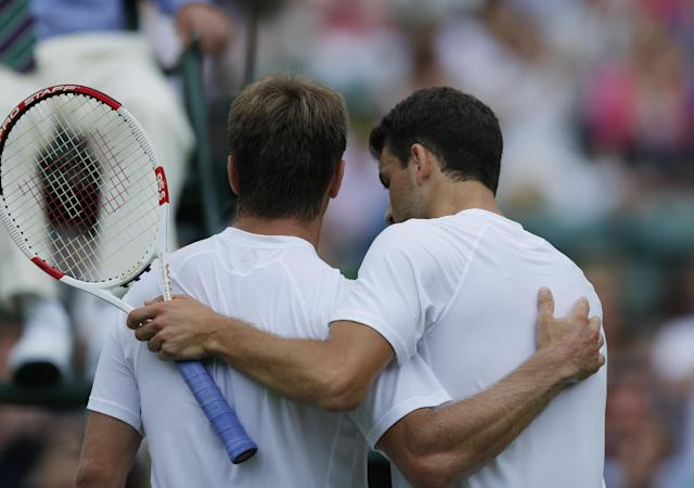 Grigor Dimitrov of Bulgaria and Ryan Harrison of the U.S. hold each others at end of their first round match at the All England Lawn Tennis Championships in Wimbledon, London, Monday, June 23, 2014. (AP Photo/Ben Curtis)