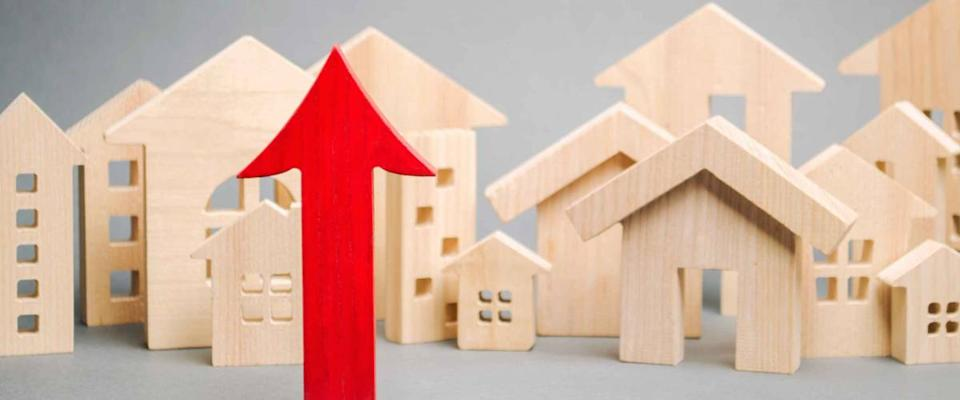 Red arrow up and miniature wooden houses. The concept of rising home prices.