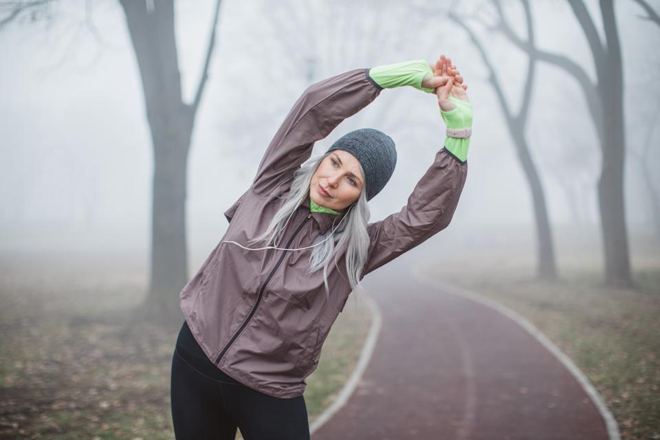 Gray hair women exercise outdoor in park, she is stretching after running. She is wearing sports clothing. Fogy and cold weather