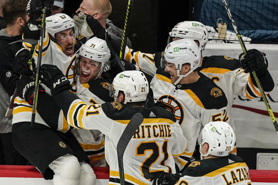 Boston Bruins center Brad Marchand, left, celebrates with teammates after scoring the winning goal in overtime of Game 2 of an NHL hockey Stanley Cup first-round playoff series against the Washington Capitals, Monday, May 17, 2021, in Washington. (AP Photo/Alex Brandon)