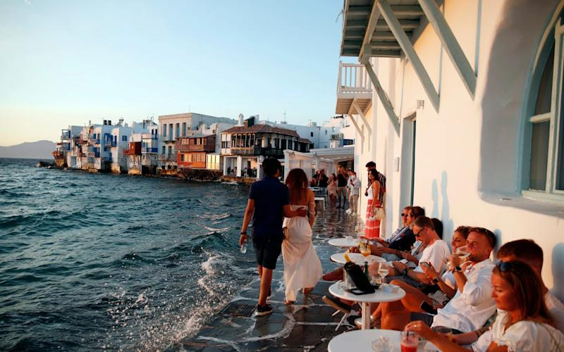 People sit at a sea-side bar in Little Venice on the Aegean Sea island of Mykonos, Greece, as the Government looks to impose local restrictions following a rise in Covid-19 cases -  Thanassis Stavrakis / AP