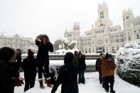 People take pictures by the Cibeles Fountain and the City Hall building during a heavy snowfall in Madrid