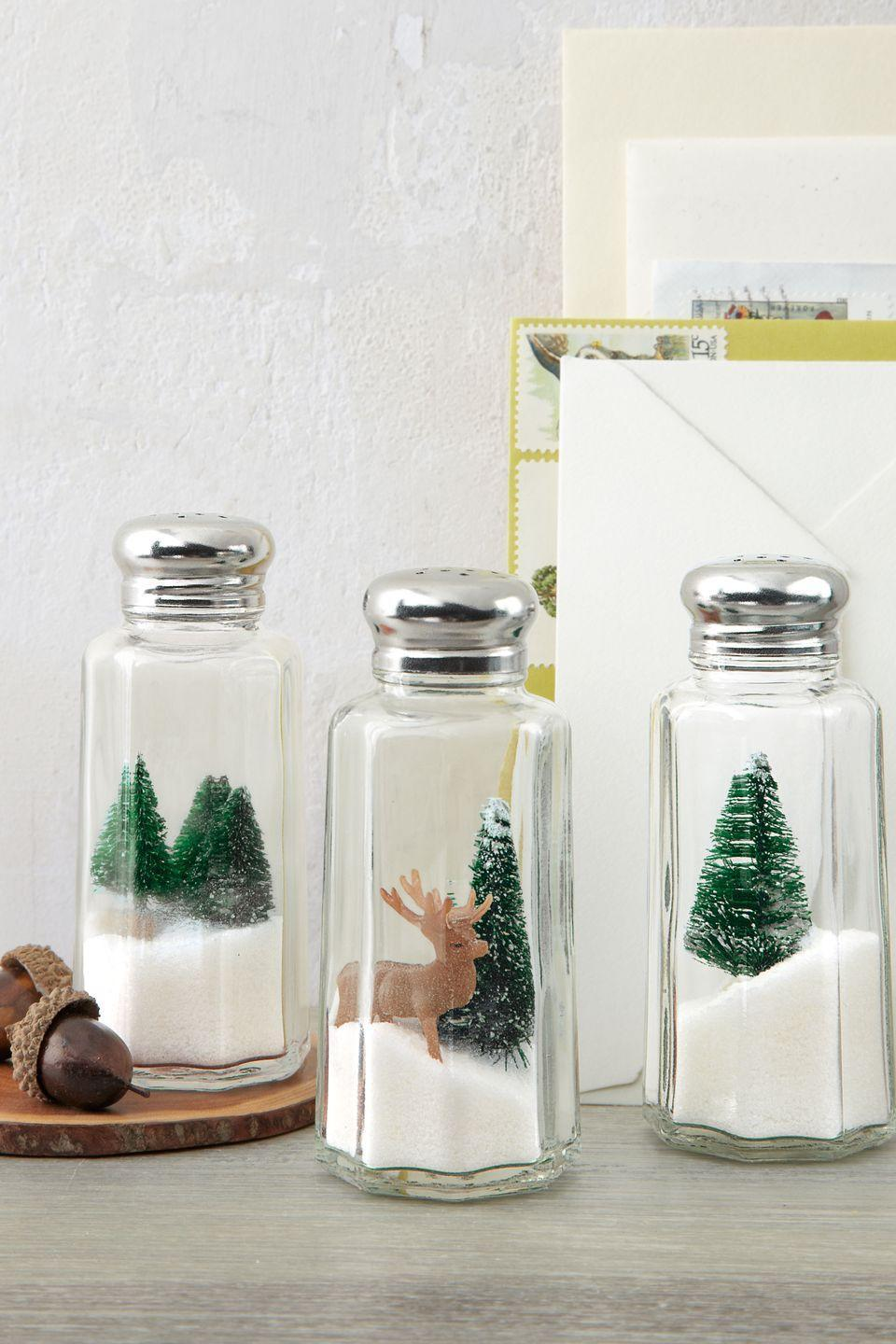 """<p>Here's one Yuletide idea that's definitely worth its salt: Turn under-a-dollar shakers into mini winter wonderlands by nesting toy evergreens and deer atop iodized """"drifts."""" </p><p><strong><a class=""""link rapid-noclick-resp"""" href=""""https://www.amazon.com/Set-12-TrueCraftware-Stainless-Mushroom/dp/B01HTWG3J8?tag=syn-yahoo-20&ascsubtag=%5Bartid%7C10050.g.645%5Bsrc%7Cyahoo-us"""" rel=""""nofollow noopener"""" target=""""_blank"""" data-ylk=""""slk:SHOP SALT SHAKERS"""">SHOP SALT SHAKERS</a></strong></p>"""
