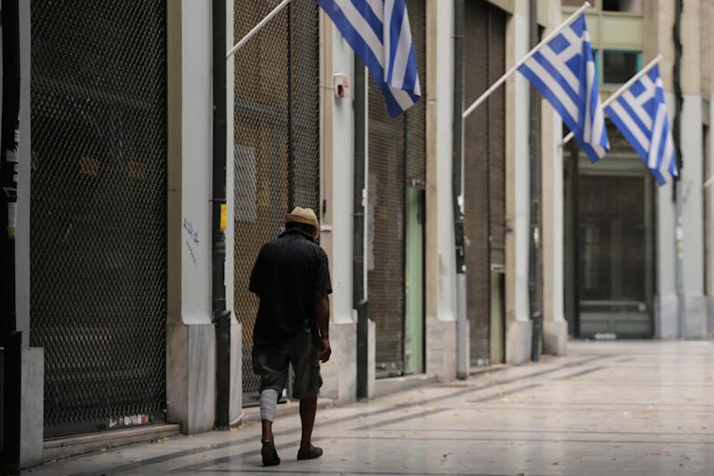 A homeless man walks next to shuttered shops in a shopping arcade decorated with Greek flags in central Athens, on Wednesday, Aug. 21, 2013. A top European Central Bank official headed to Athens on Wednesday to discuss progress on Greece's fiscal reforms, amid increasing talk the country will need yet more assistance once its bailout program ends next year. (AP Photo/Petros Giannakouris)