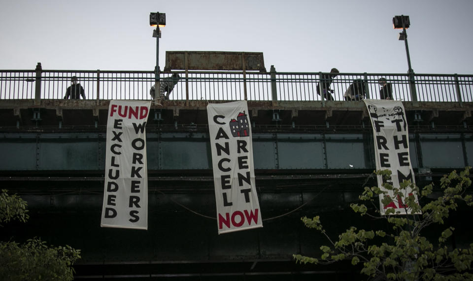 """People unfold banners from a subway platform during a vigil memorializing more than sixty persons who died from COVID-19 and were associated with Make the Road New York (MRNY), a support organization for immigrant and working class communities, Thursday May 21, 2020, in Corona Plaza, Queens, N.Y. With support from elected state and city officials, MRNY has launched a campaign called #Recovery4All, demanding Governor Cuomo and Mayor de Blasio create """"a $3.5 billion Excluded Workers' Fund, cancel rent, and release at risk people from prisons and detention centers"""" to address the disproportionate effects from the pandemic in Queens. (AP Photo/Bebeto Matthews)"""