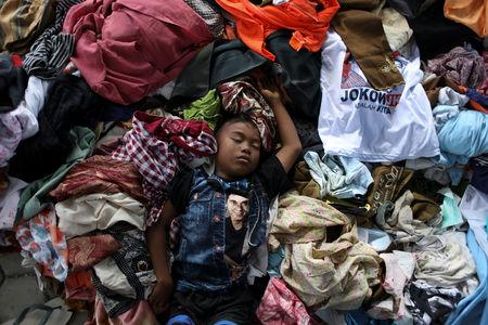 A boy sleeps over a pile of recycled clothes at a camp for displaced victims of the earthquake and tsunami in Palu, Central Sulawesi, Indonesia, October 9, 2018. REUTERS/Jorge Silva