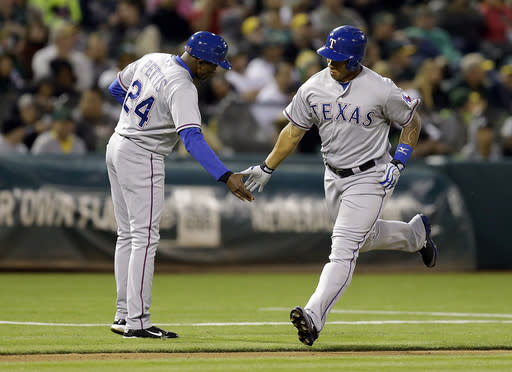 Texas Rangers' Michael Choice, right, is congratulated by third base coach Gary Pettis, left, after Choice hit a two-run home run off Oakland Athletics' Ryan Cook in the fifth inning of a baseball game Monday, June 16, 2014, in Oakland, Calif. (AP Photo/Ben Margot)