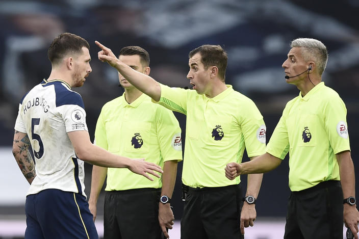 Tottenham's Pierre-Emile Hojbjerg, left, talks to referee Peter Bankes during the English Premier League soccer match between Tottenham and Newcastle at the Tottenham Hotspur Stadium in London, Sunday, Sept. 27, 2020. (Daniel Leal-Olivas/Pool via AP)