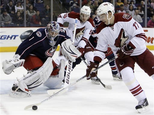 Columbus Blue Jackets' Steve Mason, left, watches after a save as Phoenix Coyotes' Radim Vrbata, right, of the Czech Republic, controls the puck and Antoine Vermette looks on during the first period of an NHL hockey game Tuesday, March 6, 2012, in Columbus, Ohio. (AP Photo/Jay LaPrete)