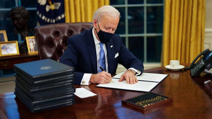 President Joe Biden signs his first executive orders in the Oval Office of the White House in Washington on Wednesday, Jan. 20, 2021. President Biden, vowing to restore environmental protections frayed over the past four years, has ordered the review of more than 100 rules and regulations on air, water, public lands, endangered species and climate change that were weakened or rolled back by his predecessor.