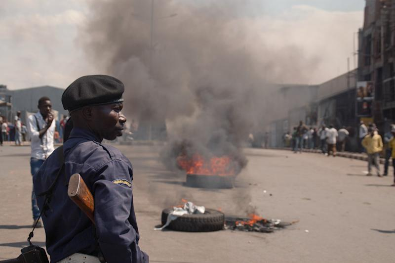 A police officer looks on as protestors burn tires in the street following recent violence, including mortar attacks that have struck homes and churches in the eastern provincial capital, killing at least seven civilians and wounding dozens of others, in Goma, Congo, Saturday, Aug. 24, 2013. Congolese soldiers supported by U.N. forces fought rebels in the country's deteriorating east for hours early Saturday, officials said, while a rocket landed inside the town of Goma and killed three people. Congo immediately blamed the attacks on neighboring Rwanda, which has long been accused of supporting the eastern Congolese rebel movement known as M23. (AP Photo/Joseph Kay)