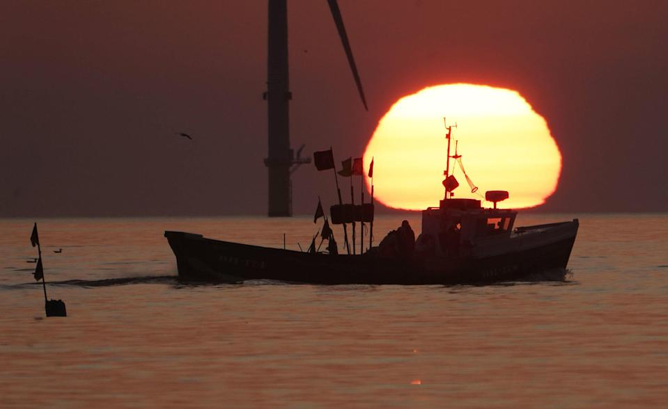 A fishing boat sails in front of the rising sun near Blyth pier in Northumberland (PA)