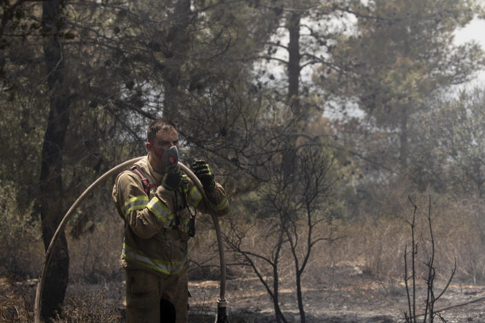 An Israeli firefighter pauses to put on a mask while battling wildfires for the second day near Shoresh, on the outskirts of Jerusalem, Monday, Aug. 16, 2021. Israel Fire and Rescue service said in a statement Monday that 45 firefighting teams accompanied by eight planes were working to contain five fires in the forested hills west of the city. (AP Photo/Maya Alleruzzo)