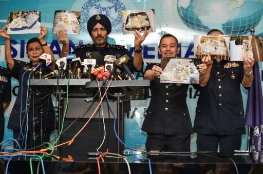 Malaysian police hold up pictures of jewellery and other items seized in raids on properties linked to the former first couple. The items were estimated to be worth more than $270 million
