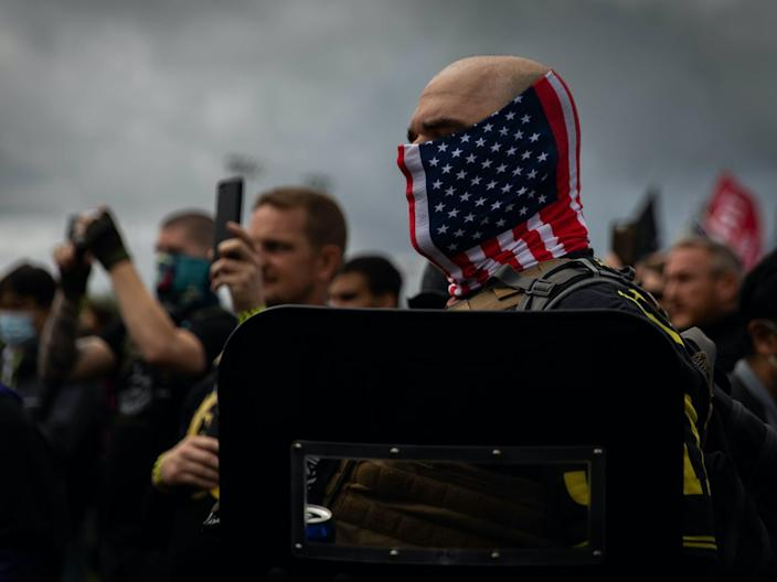 """A man hold his hand to his heart as a Proud Boys organizer recites the Pledge of Allegiance during a Proud Boys rally. <p class=""""copyright"""">MARANIE R. STAAB/AFP via Getty Images</p>"""