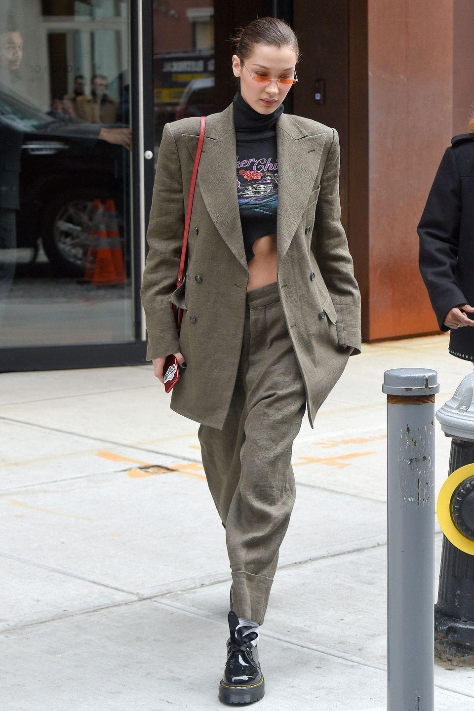 <p>In New York City, wearing a black crop-top turtleneck, under a moss green suit coat and matching pants, with short Doc Marten boots, and orange-tinted small-frame sunglasses.</p>