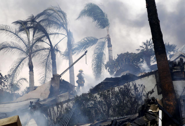 <p>A firefighter stands under windswept palm trees as he hoses down smoldering debris in Ventura, Calif., Tuesday, Dec. 5, 2017. (Photo: Daniel Dreifuss via AP) </p>