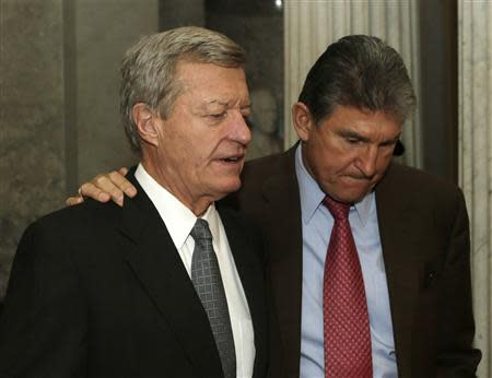 Senators Max Baucus (D-MT) (L) and Joe Manchin (D-WV) walk out of the Senate chamber after voting on the U.S. budget bill in Washington December 18, 2013. REUTERS/Gary Cameron