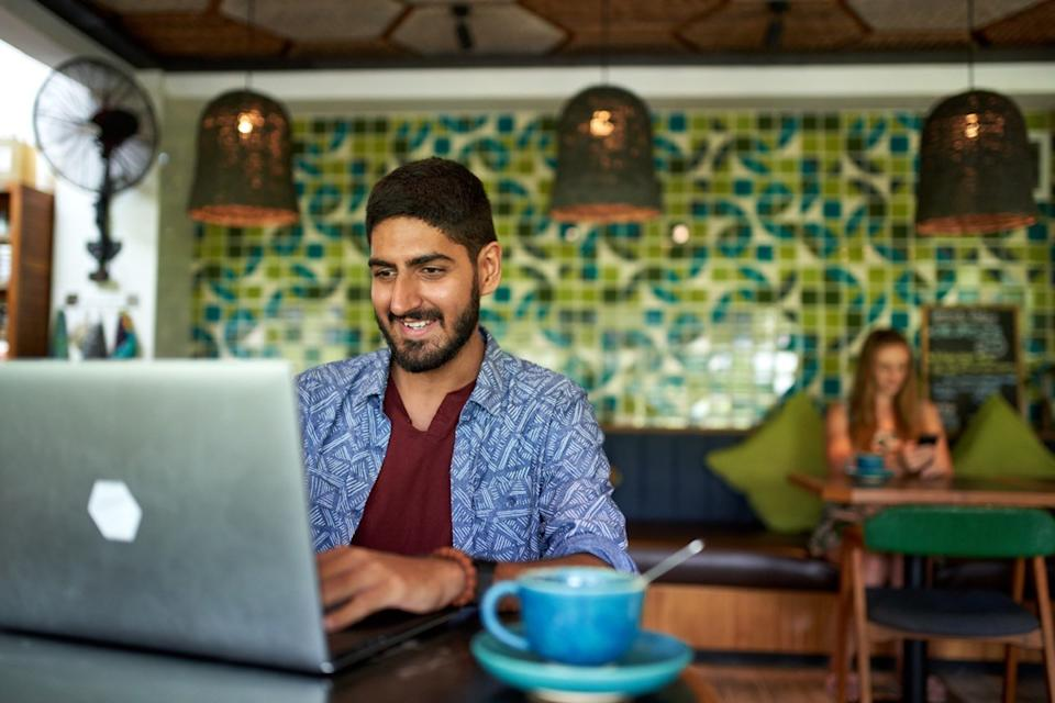 young man working on a laptop at a coffee shop