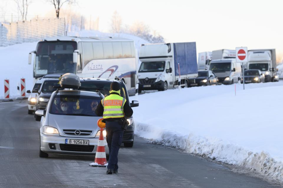 Cars and trucks from the Czech Republic stand one behind the other at a rest area on highway 17 during border controls by the German Federal Police in Bad Gottleuba, Germany, Sunday, Feb. 14, 2021. Germany has implemented tighter border controls on its frontiers with the Czech Republic and Austria's Tyrol province in an effort to stem the spread of more contagious coronavirus variants. (Sebastian Kahnert/dpa via AP)