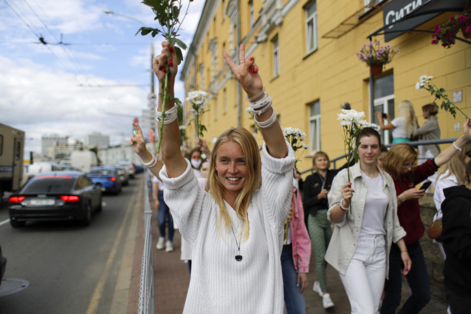 "A Belarusian woman shows a victory sign during a rally in solidarity with protesters injured in the latest rallies against the results of the country's presidential election in Minsk, Belarus, Thursday, Aug. 13, 2020. Hundreds of people were back on the streets of Belarus' capital on Thursday morning, forming long ""lines of solidarity"" in protest against an election they say was rigged to extend the rule of the country's authoritarian leader and against a crackdown on rallies that followed the vote. (AP Photo/Sergei Grits)"
