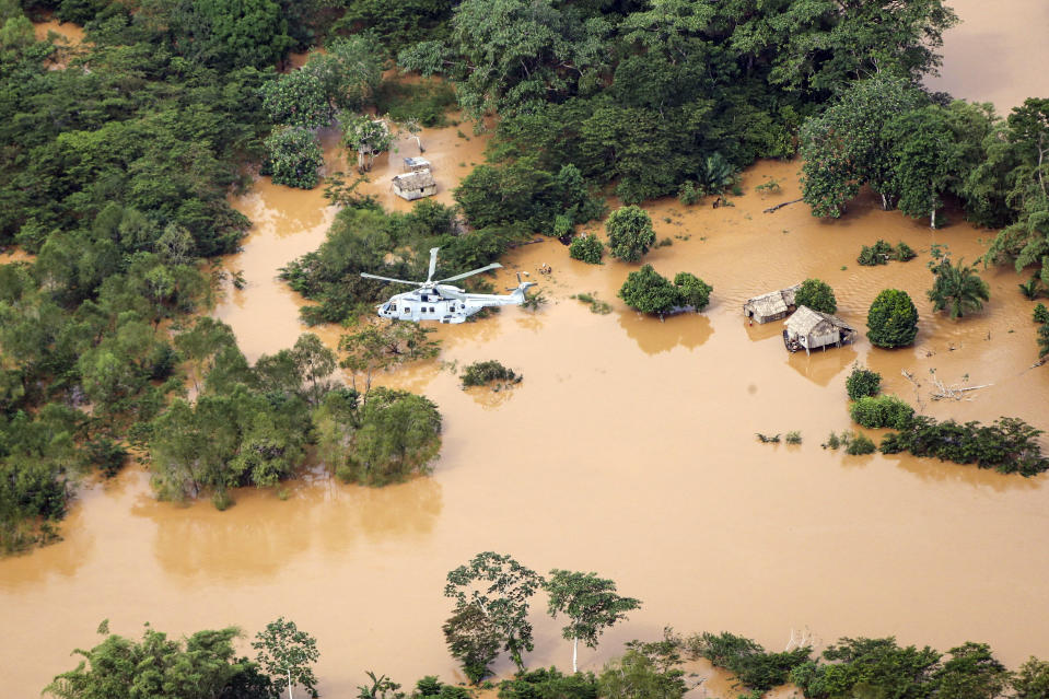 In this undated handout photo provided by the Ministry of Defence on Saturday, Nov. 21, 2020, a Merlin Helicopter from 845 Naval Air Squadron conducting damage surveys in Honduras. The devastation caused by Hurricane Iota is becoming clear as communications are restored after the second Category 4 hurricane in two weeks to blast Nicaragua's Caribbean coast. The official death toll rose in Nicaragua with victims swept away by swollen rivers or buried in landslides. (LPhot Robert Oates/Ministry of Defence via AP)