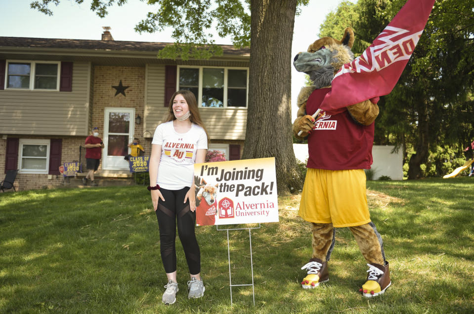 Muhlenberg Township, PA - May 26: Incoming Alvernia freshman Samantha Hensel, 18, laughs and poses with the Alvernia mascot in her Muhlenberg Township front yard during a parade celebrating Alvernia University's incoming freshmen. Tuesday, May 26, 2020.  They brought the sign for her yard. (Photo by Lauren A. Little/MediaNews Group/Reading Eagle via Getty Images)