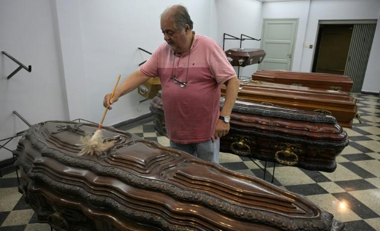 Eduardo Tapia uses a duster to clean coffins for sale in the Buenos Aires funeral home he owns, where he and his colleagues constantly are forced to lower their prices