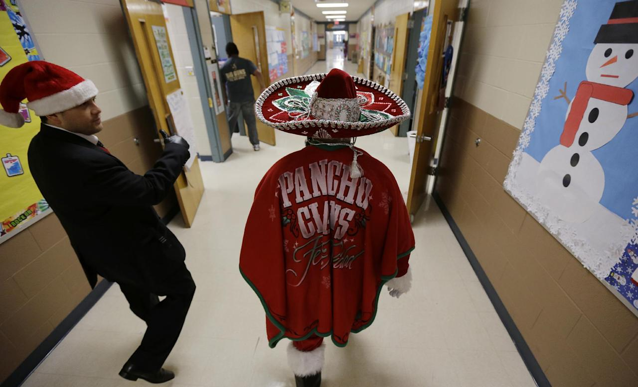 In this Friday, Dec. 20, 2013, photo, Pancho Claus, Rudy Martinez, right, walks through the halls of Knowlton Elementary School as he visits students, in San Antonio. Pancho Claus, a Tex-Mex Santa borne from the Chicano civil rights movement in the late 1970s and early 1980s, is now an adored Christmas fixture in many Texas cities. (AP Photo/Eric Gay)