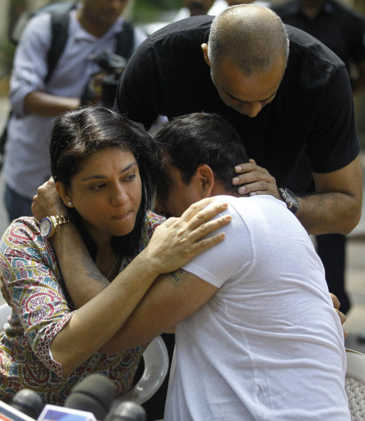 Indian Bollywood actor Sanjay Dutt, right, breaks down as his sister Priya Dutt tries to console him during a press conference at his residence in Mumbai, India, Thursday, March 28, 2013. Dutt said he has not sought pardon for a 1993 weapons conviction and will serve his prison sentence as ordered by India's Supreme Court. Dutt broke his silence a week after the court sentenced him to five years in prison for illegal possession of weapons supplied by Mumbai crime bosses linked to a 1993 terror attack that killed 257 people.(AP Photo/Rafiq Maqbool)