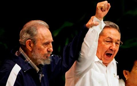 2011: Fidel Castro, left, raises his brother's Raul's hand, as they sing the anthem of international socialism during the 6th Communist Party Congress in Havana - Credit: Javier Galeano/ AP