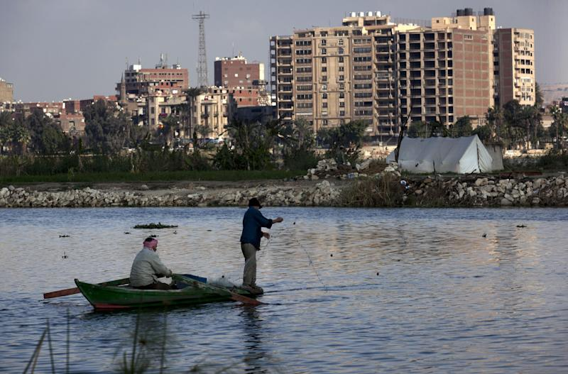 Two Egyptian fishermen work on their boat at the Nile river surrounding the Qursaya island, in Cairo, Egypt, Monday, Jan. 14, 2013. The Egyptian Armed Forces claims that it is the registered owner of the island's land, a claim disputed by the some 5,000 farmers and fishermen residents of the embattled island that have been resisting their eviction since 2007. (AP Photo/Nasser Nasser)