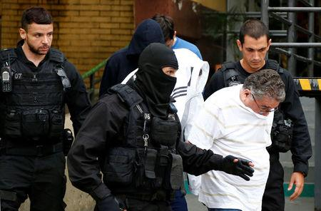 """People detained during the probe known as """"Operation Weak Flesh"""" are escorted by the police as they leave the Institute of Forensic Science in Curitiba"""