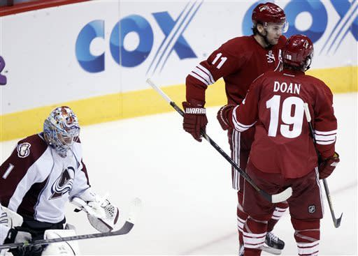 Phoenix Coyotes center Martin Hanzal, center ,of the Czech Republic, congratulates teammate Shane Doan, right, after Doan scored a goal against Colorado Avalanche goalie Semyon Varlamov, left, of Russia, in the second period of NHL hockey game Saturday, April 6, 2013, in Glendale, Ariz. (AP Photo/Paul Connors)