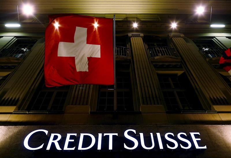 Logo of Swiss bank Credit Suisse seen below the Swiss national flag at a building in the Federal Square in Bern