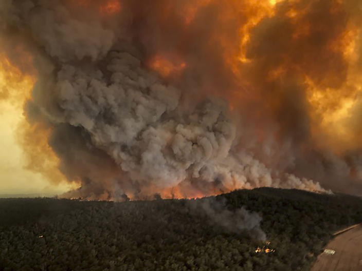 Wildfires rage under plumes of smoke in Bairnsdale, Australia, on Monday. (Glen Morey via AP)