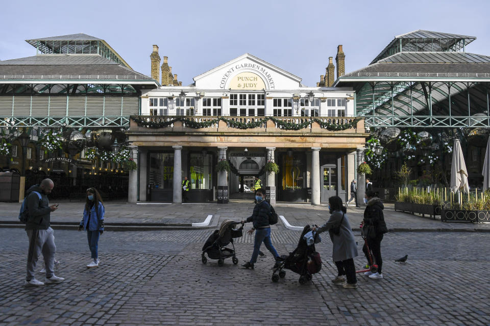 People walk in the near empty area of Covent Garden, in London, Tuesday, Nov. 24, 2020. Haircuts, shopping trips and visits to the pub will be back on the agenda for millions of people when a four-week lockdown in England comes to an end next week, British Prime Minister Boris Johnson said Monday. (AP Photo/Alberto Pezzali)