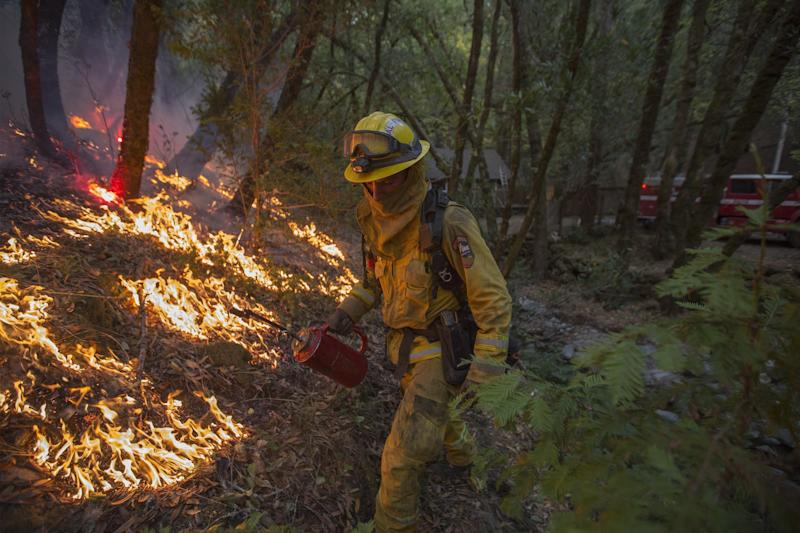 A firefighter uses a drip torch to set a backfire to protect houses in Adobe Canyon during the Nuns Fire on Oct. 15, 2017 near Santa Rosa, California. (David McNew via Getty Images)