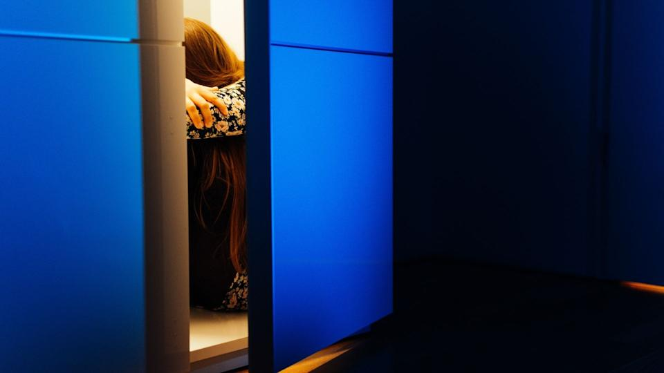 Woman hides in cupboard after experiencing domestic violence.
