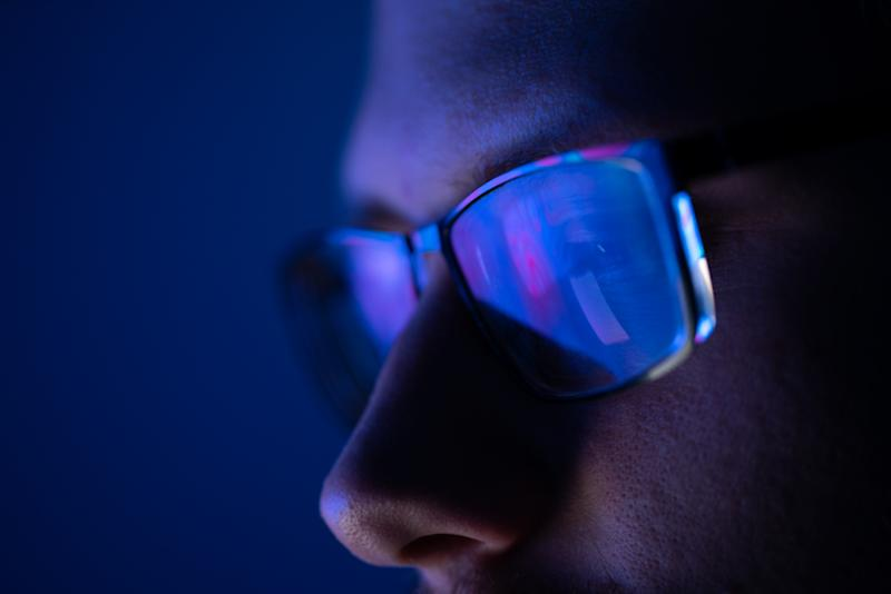 Close-up of a part of a male human face with glasses in neon light