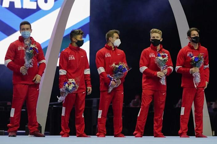 Members of the U.S. Men's Olympic Team wear masks and hold flowers while standing on stage