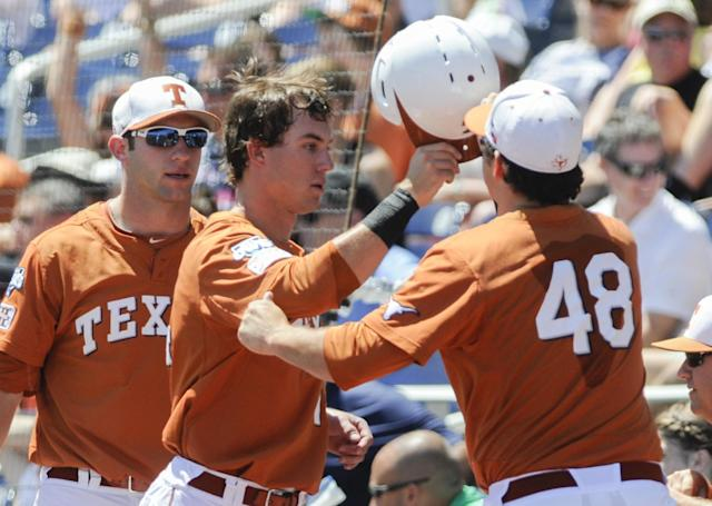 Texas' Ben Johnson, center, is greeted at the dugout by Ty Marlow (48) and catcher Jacob Felts, left, after scoring against Vanderbilt in an NCAA baseball College World Series game in Omaha, Neb., Friday, June 20, 2014. (AP Photo/Eric Francis)
