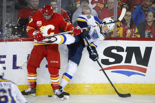 St. Louis Blues' Sammy Blais, right, is checked by Calgary Flames' T.J. Brodie during the second period of an NHL hockey game in Calgary, Saturday, Nov. 9, 2019. (Jeff McIntosh/The Canadian Press via AP)