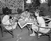 """<p>Lucille Ball and Desi Arnaz enjoy breakfast al fresco with their three Cocker Spaniels in 1942. The newlyweds moved onto a five-acre ranch in San Fernando Valley, which they appropriately named <a href=""""https://venturablvd.goldenstate.is/lucy-in-the-valley/"""" rel=""""nofollow noopener"""" target=""""_blank"""" data-ylk=""""slk:Desilu Ranch"""" class=""""link rapid-noclick-resp"""">Desilu Ranch</a> in 1941. </p>"""